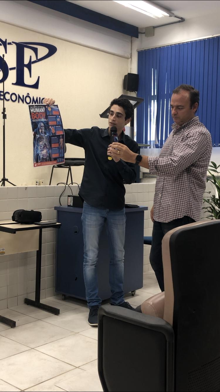 Rafael More e Luciano Castro mostram um pôster do corpo humano.